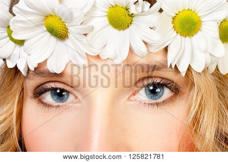 Close-up image of a woman's beautiful blue eyes with chamomile wreath