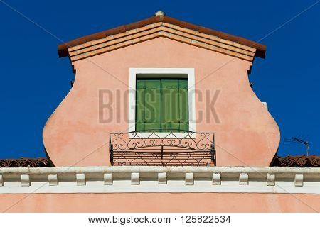 Roof with green window of old italian house on Murano Island in Venice, Italy
