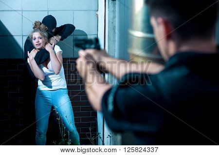 Policeman is pointing gun at armed kidnapper