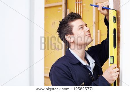 Male Builder Checking Work With Spirit Level