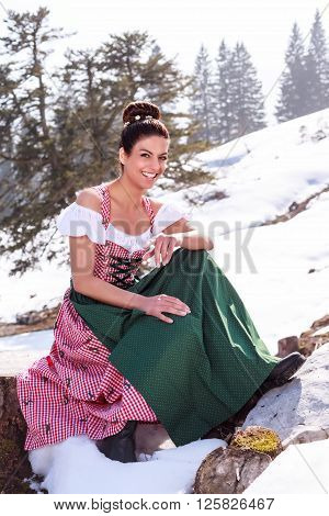 Woman sitting in Dirndl on a stump in the snow and pointing his finger smiling at the camera.