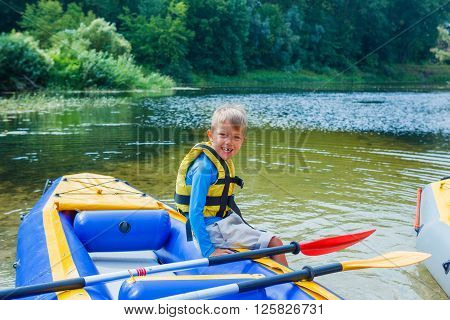 Active happy child having fun adventurous experience kayaking on the river on a sunny day during summer vacation