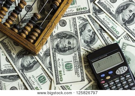 Background texture of banknotes in denominations of one hundred dollars scattered on a table and an old wooden abacus with calculator