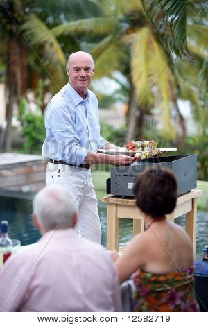 Senior man preparing skewers on a plancha in front of his friends