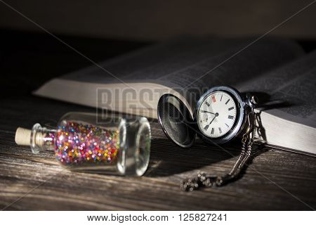 A small glass bottle with a bright colorful shiny beads and cork lid lies next to the old pocket watch and an open book illuminated by a light bulb. Photo in low key. Focus on watch