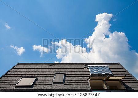 Solar water panel with dormers on a roof against blue sky