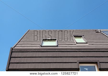 Solar Blinds and Roof Window on new wooden house against blue sky