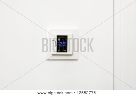 White digital climate control on white wall