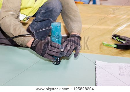 Building a wall for frame house. Worker use Laminate Trimmer for cutting drywall