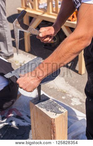 Worker produces roofing slate using a slate hammer