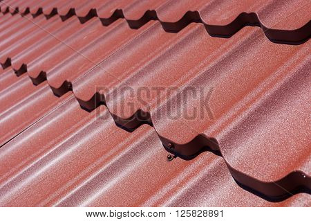 Brown metal tile with screw close up