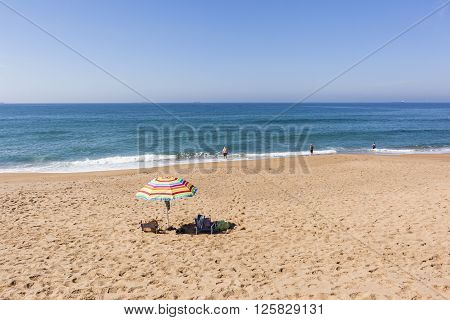 Beach blue ocean waters with holiday bathers swimming coastline landscape.