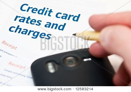 Hand Holding Pen Over Cedit Card Rates