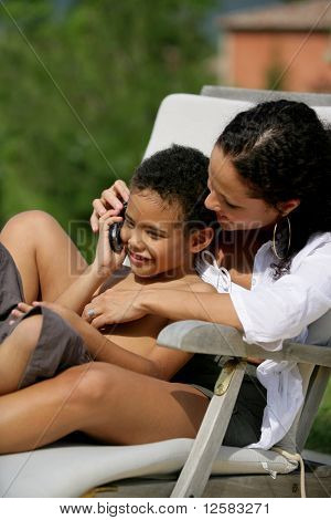 Smiling woman sitting on a deckchair with a little boy phoning