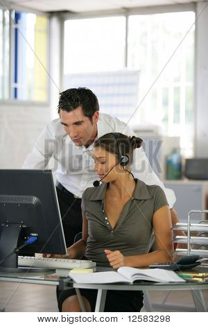 Man at a computer near a woman with a headset