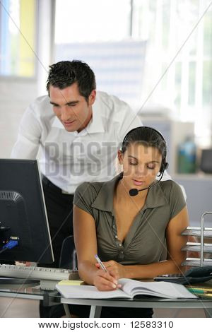Young man in suit in front of a desktop computer near a young woman with headset