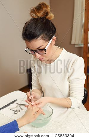 Manicure process in a beauty salon. Manicurist in glasses preparing fingernails to manicure.