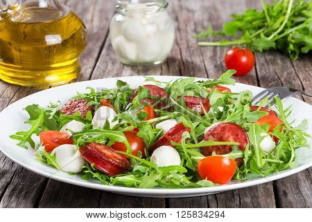 Salad with tomatoes mozzarella arugula sausages on a white dish on a rustic table balls of mozzarella cheese in a glass jar and bottle of olive oil on the background studio light close-up