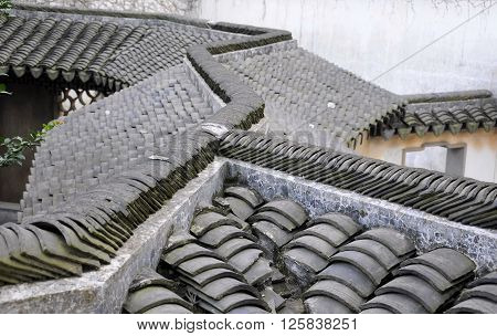 The slated tile roofs of the weathered buildings within Tongli Town in Jiangsu province china.