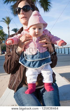 two month age baby red blue and white clothes open eyes funny expression face standing on legs holding in hands of brunette woman mother with brown jacket sitting in street outdoor