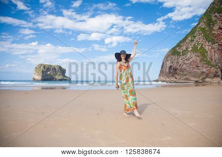 brunette adult woman with black hat and big vintage floral dress looking and dancing happy on sand at Ballota beach with ocean and island behind in Asturias Spain