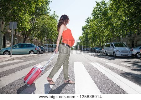 brunette brown hair pregnant woman with orange shirt green trousers in summer walking with suitcase on crosswalk in Madrid urban street