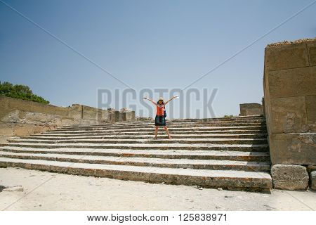 woman traveler tourist open arms in landmark stairs of Festo or Festos palace ruins from XV century Before Christ Minoan greek city monument in Crete Greece Europe