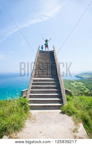 happy woman looking with open arms up on top of spectacular high stone stairs scenic viewpoint over water ocean nature and mountain in Mirador del Fito in Cangas de Onis Asturias Spain