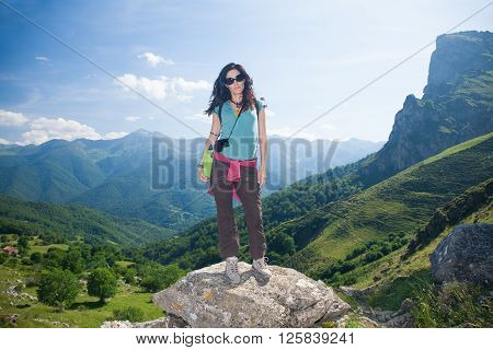 brunette sport hiking or trekking woman with green shirt brown trousers posing looking over valley and mountain in Picos de Europa natural park in Cantabria Spain