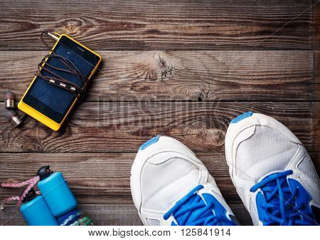 Sports equipment - sneakers, skipping rope, smartphone and headphones. Sport background on wooden floor, top view.
