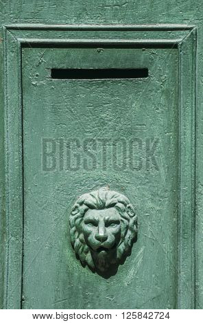 Slit of green metal mailbox with lion's head ornament