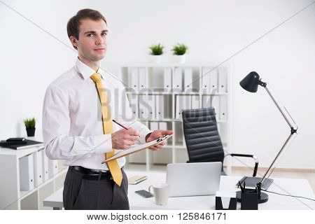 Businessman with notepad standing in office. Concept of work.