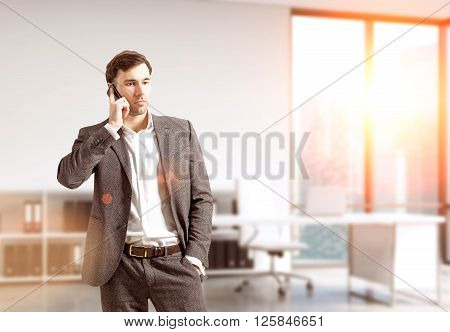 Businessman talking on the phone in sunlit office