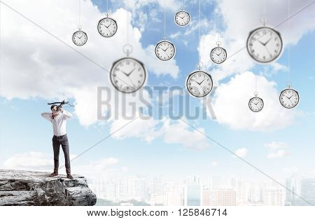 Archer standing on the edge of a cliff aiming at suspended clocks on sky background
