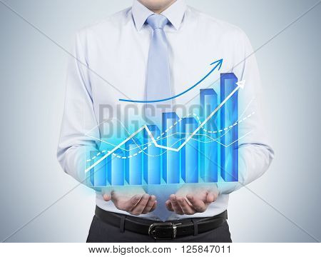 Businessman holding bar chart and graphs drawn on virtual screen. Chest view. Concept of business analysis.