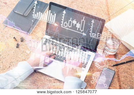 Businessman typing on laptop glass of water smartphone and notebooks aside. Only hands seen. Double exposure. Concept of work.