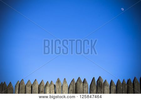 Palisade stockade palings logs and blue sky. Abstract background old ancient.