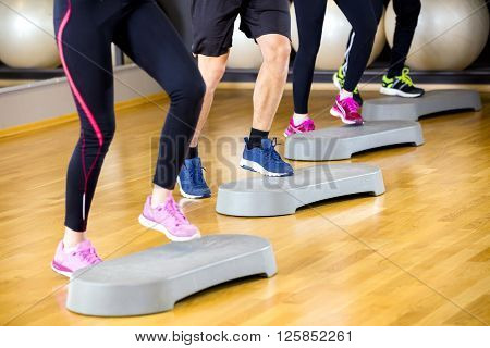 Close-up of people in a team raises legs at step platform in a fitness gym class. Stamina and body coordination workout. Teamwork and motivation.