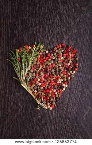 a mixture of peppers ( red white black ) in the form of heart with a sprig of rosemary on a black background