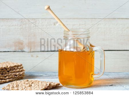 honey with dipper and crispbread on wooden background ** Note: Shallow depth of field