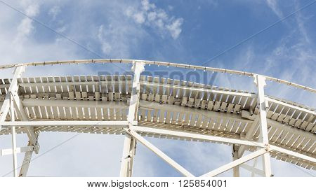abstraction made of white wood of the old road on the background of blue sky with white cumulus and cirrus clouds