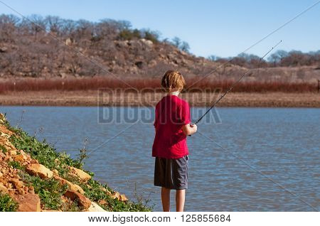 Young boy on a pond catching a fish.