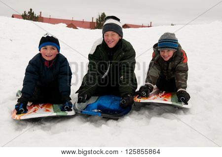 Portrait of cute boys being silly on a sled in the snow.