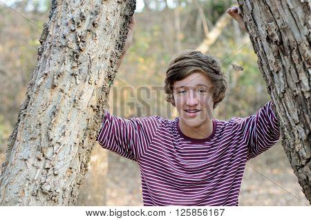Portrait of cute teenage boy standing between trees outdoors.