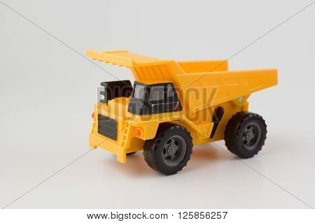 toy car dump truck is yellow on a white background