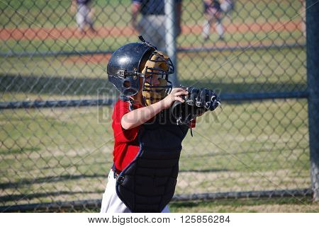 Youth baseball player catching during a little league game.