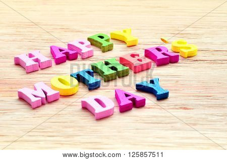 Happy Mothers Day colorful letters spelling greeting on rustic wood table
