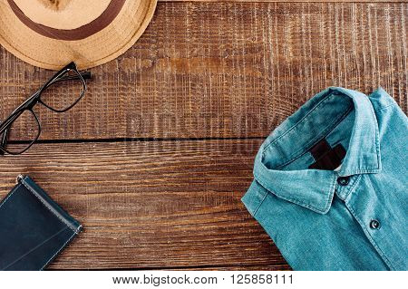 Top view photo of objects on wooden table. There are men's denim shirt, hat, glasses and purse. Free space for logo
