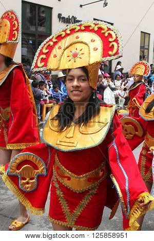 Cajamarca Peru - February 7 2016: Young Peruvian woman in red and gold costume marching in parade during Carnival in Cajamarca Peru on February 7 2016.
