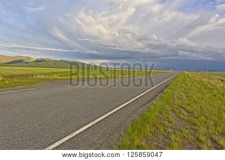 A thunderstorm building up in the distance over a deserted road in Montana.
